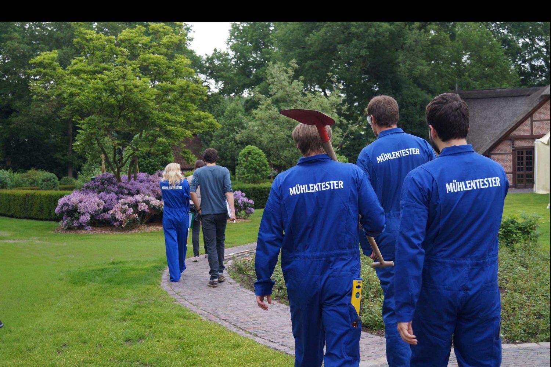 Actors in blue overalls