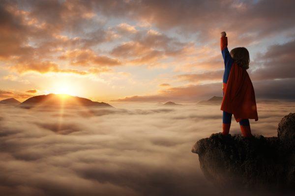 Kind in Superman-Kostüm auf dem Gipfel eines Berges